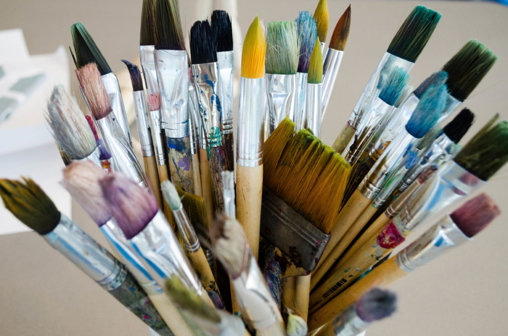 numerous painbrushes in a cup